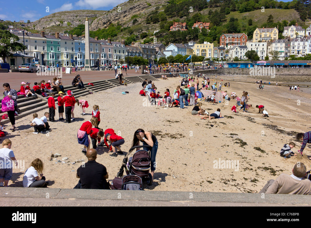 A party of school children visit Llandudno beach, with teachers and assistants, mingle with visitors on a sunny - Stock Image