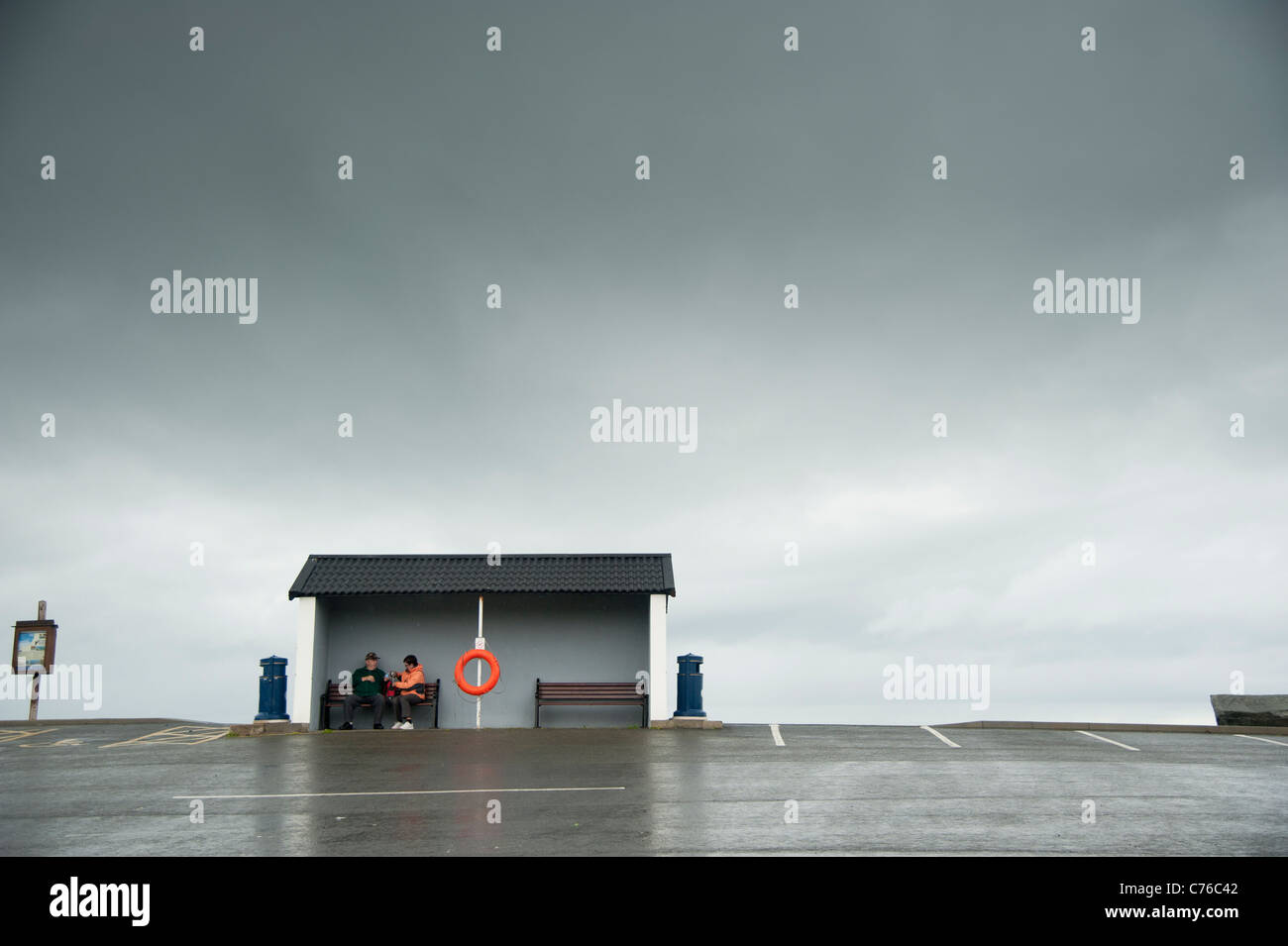 two people sheltering from the rain on a grey overcast rainy wet afternoon, Aberaeron Wales UK - Stock Image