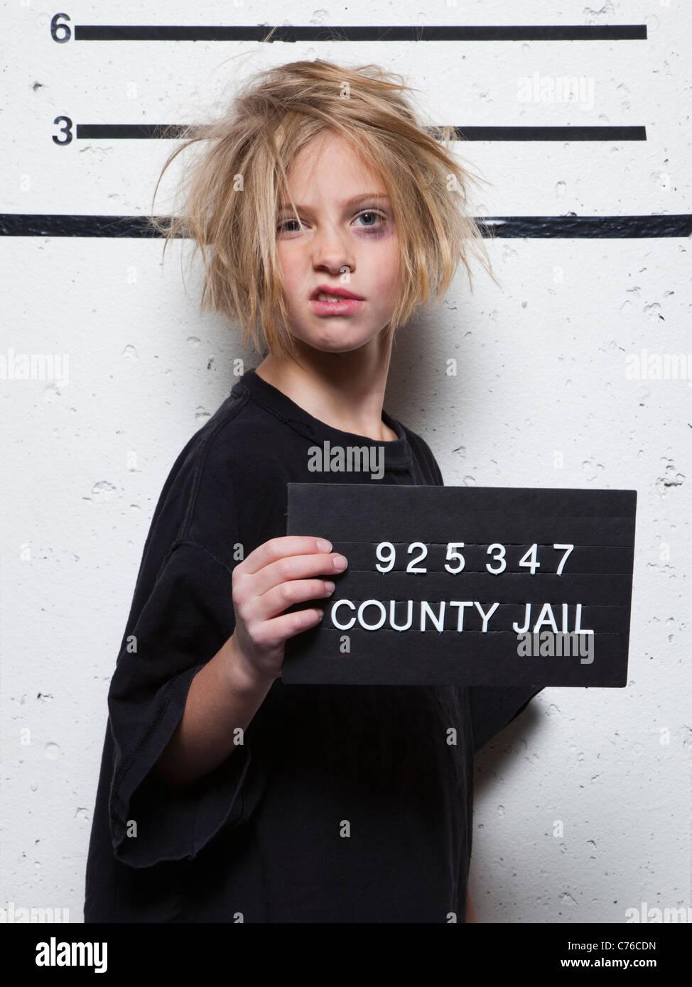 Studio mugshot of girl (8-9) with tousled hair - Stock Image
