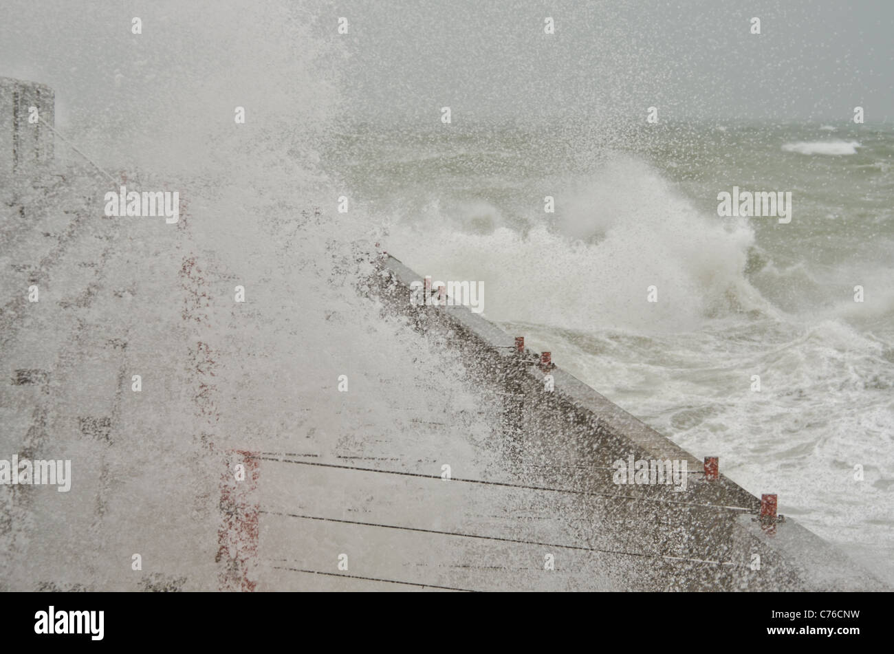 Gale force winds bring huge waves to pound the harbour wall Brighton Marina East Sussex. - Stock Image