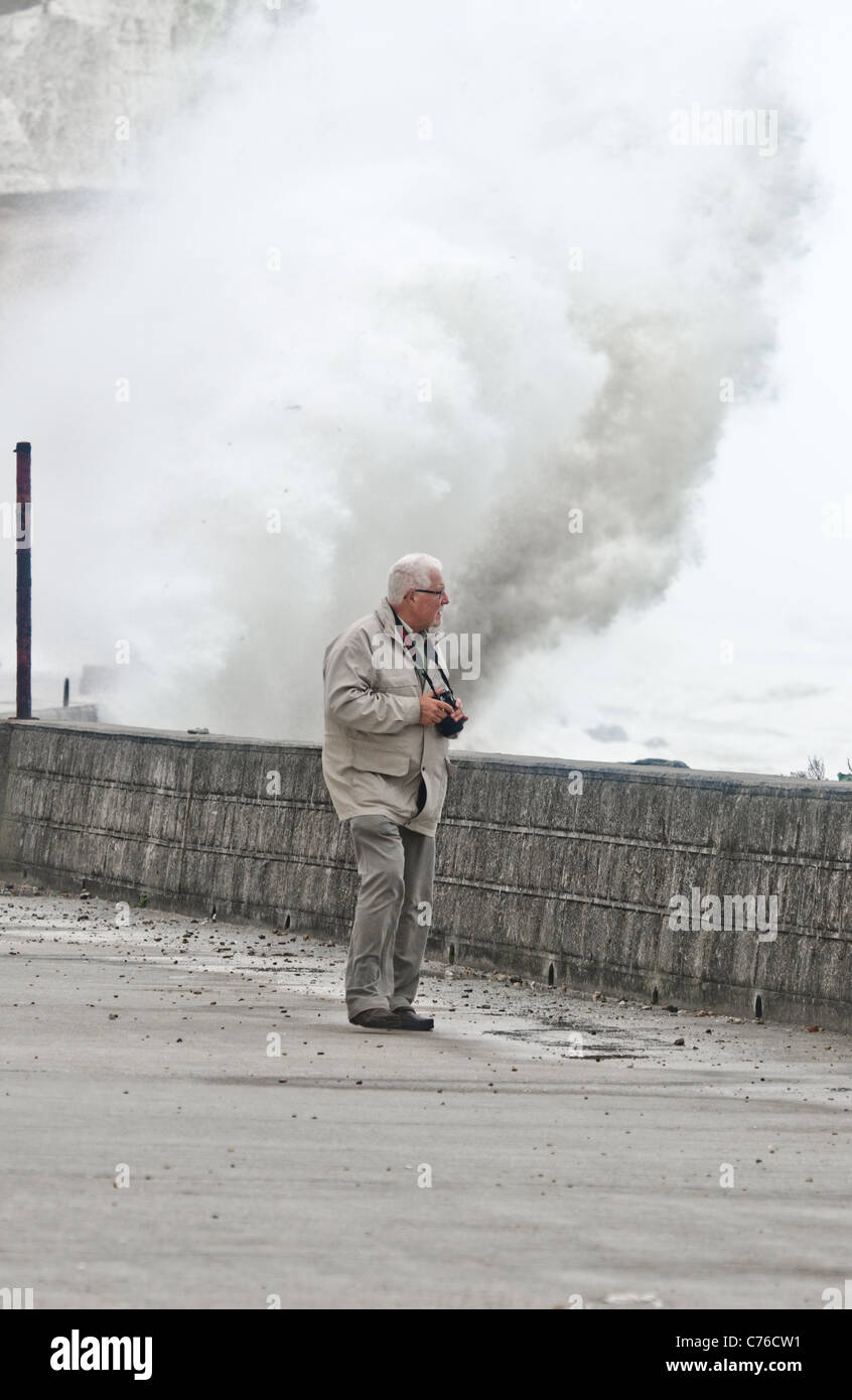 bad weather as man walks on sea defenses promenade and waves crash against the shore - Stock Image