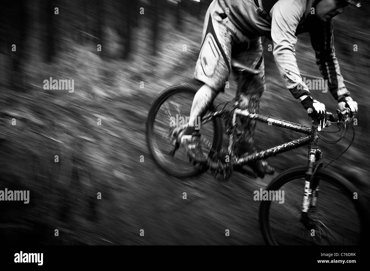 Mud covered mountain bike and rider on single track Black and White - Stock Image