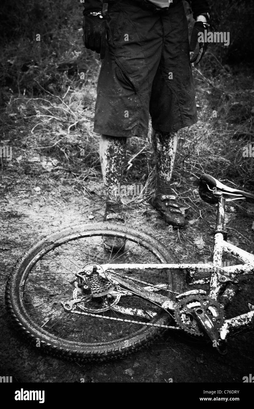 Mud covered mountain bike and rider Black and White - Stock Image