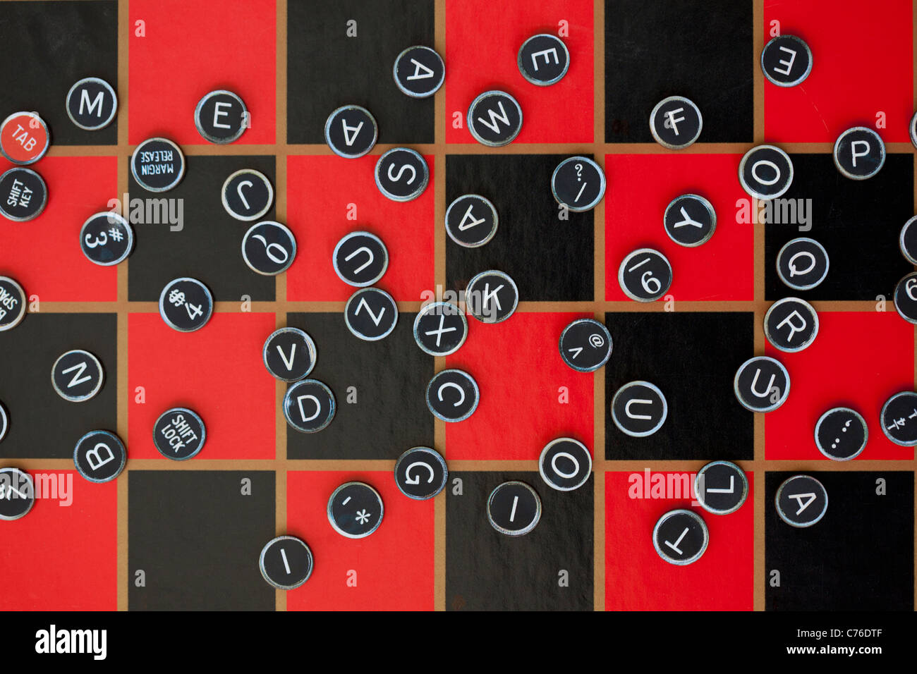 random assortment of typewriter keys on checker board - Stock Image