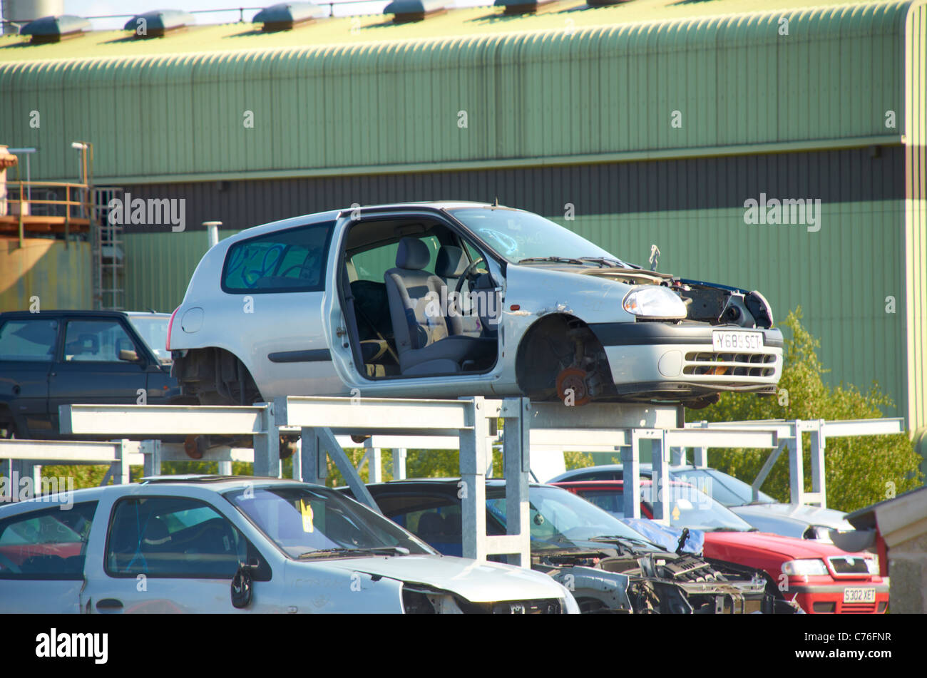 Cars stacked up in a scrapyard. - Stock Image