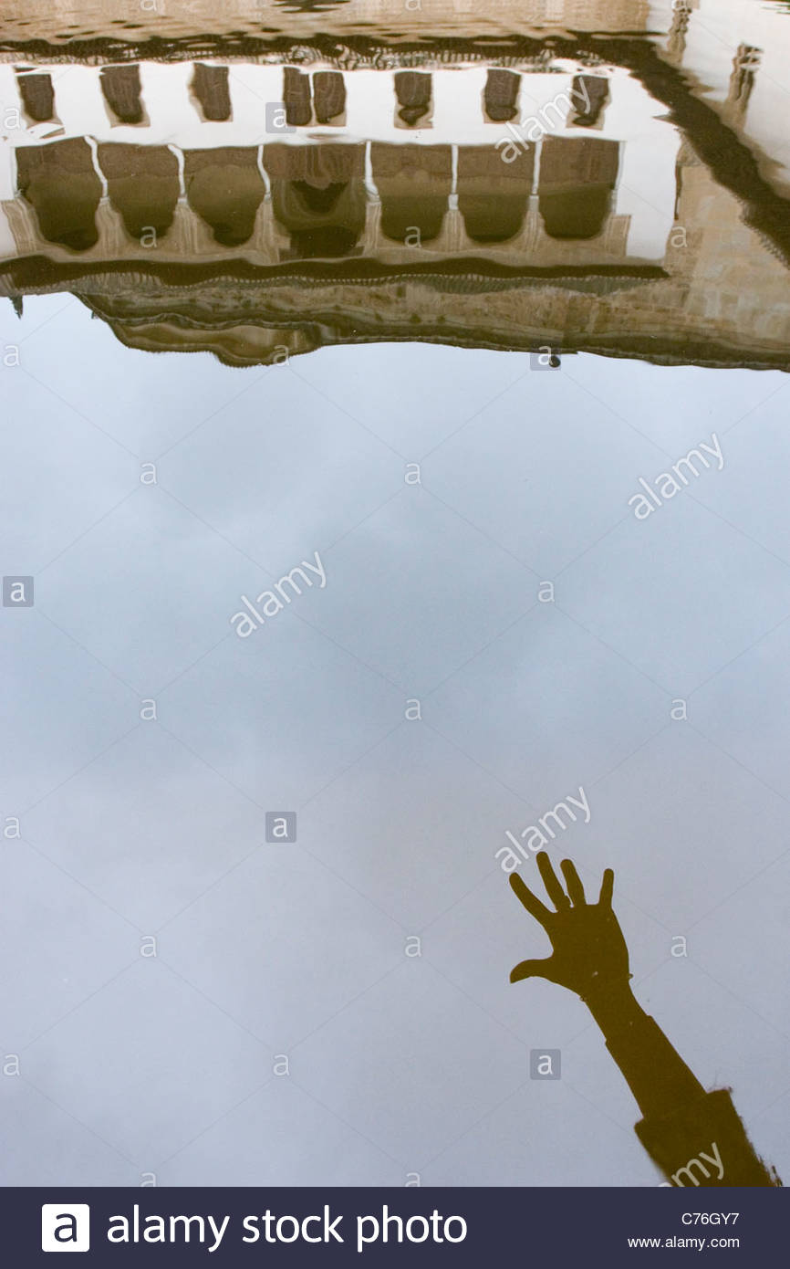 Reflection on water of a reaching hand in Comares courtyard in la Alhambra (Granada). - Stock Image