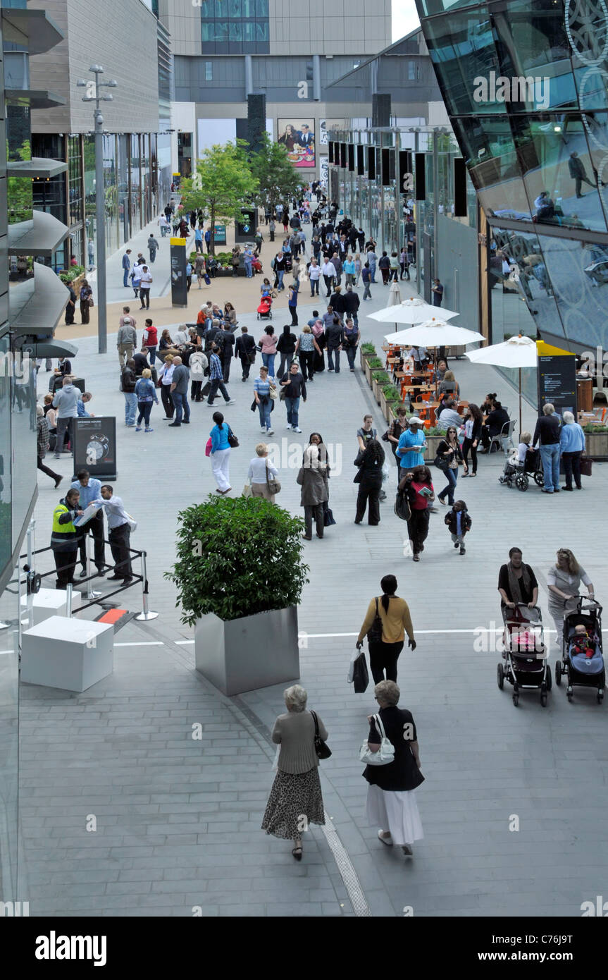 View from above looking down on people shoppers in busy outdoor Mall at the Stratford City Westfield shopping centre - Stock Image
