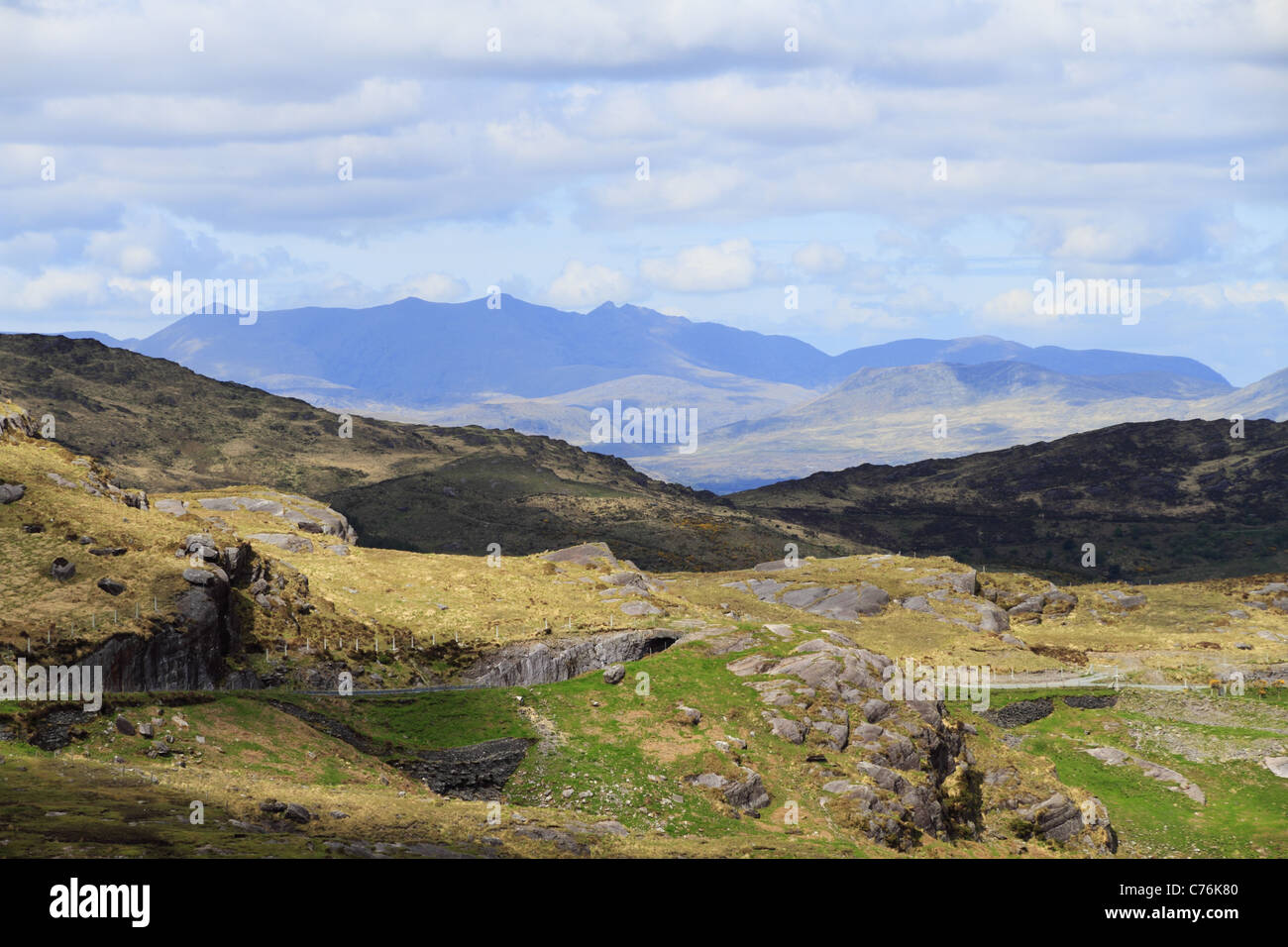 A mountain road cuts through the hills of Kerry, with MacGillycuddy's Reeks in the background, the highest mountains - Stock Image