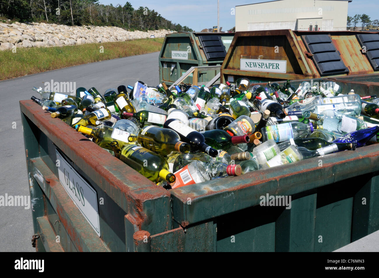 Full dumpster of glass bottles for recycling at a landfill & recycling transfer station in Bourne, Cape Cod, - Stock Image