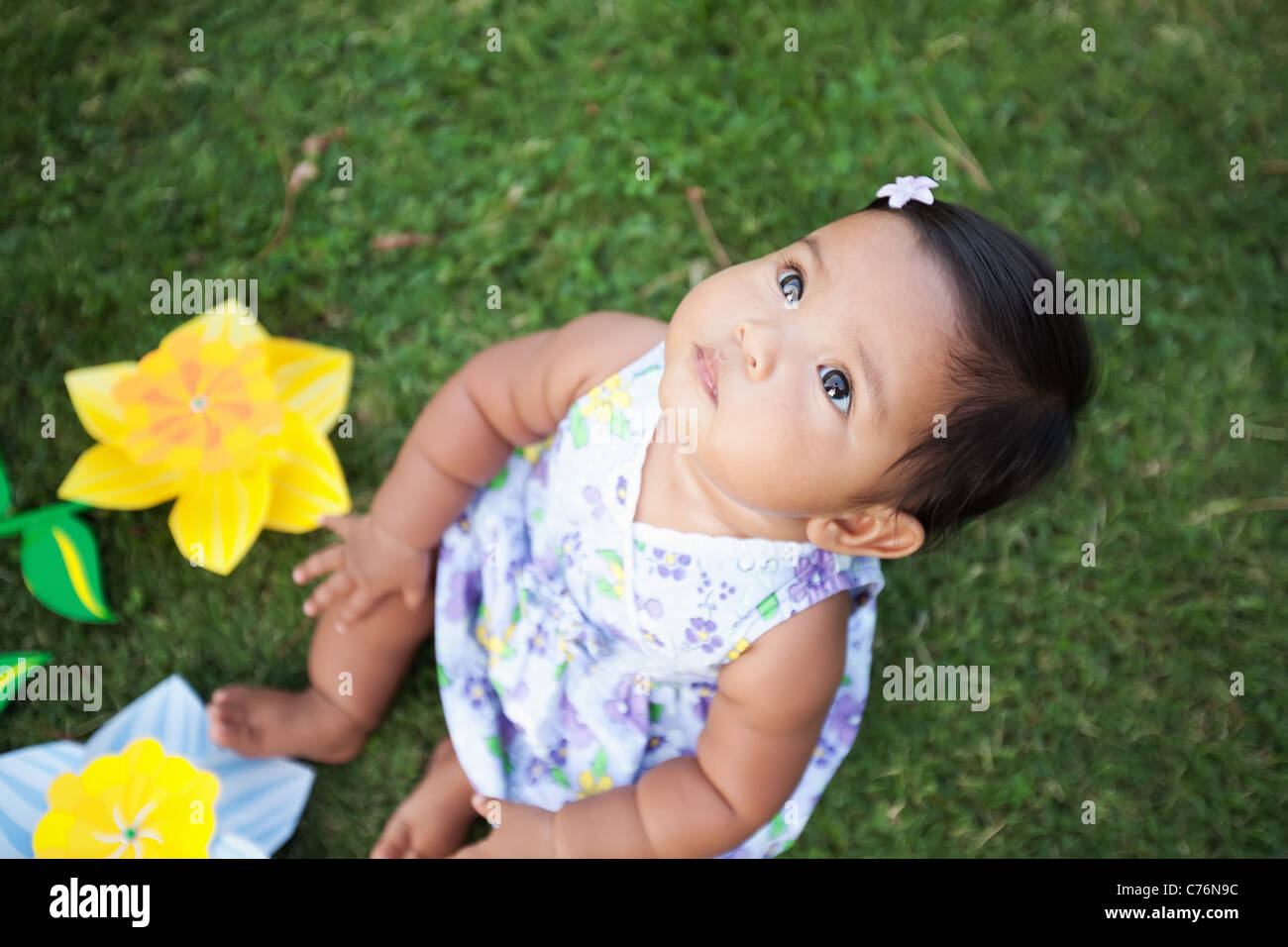 cute baby girl looking up at the sky sitting on the lawn with stock