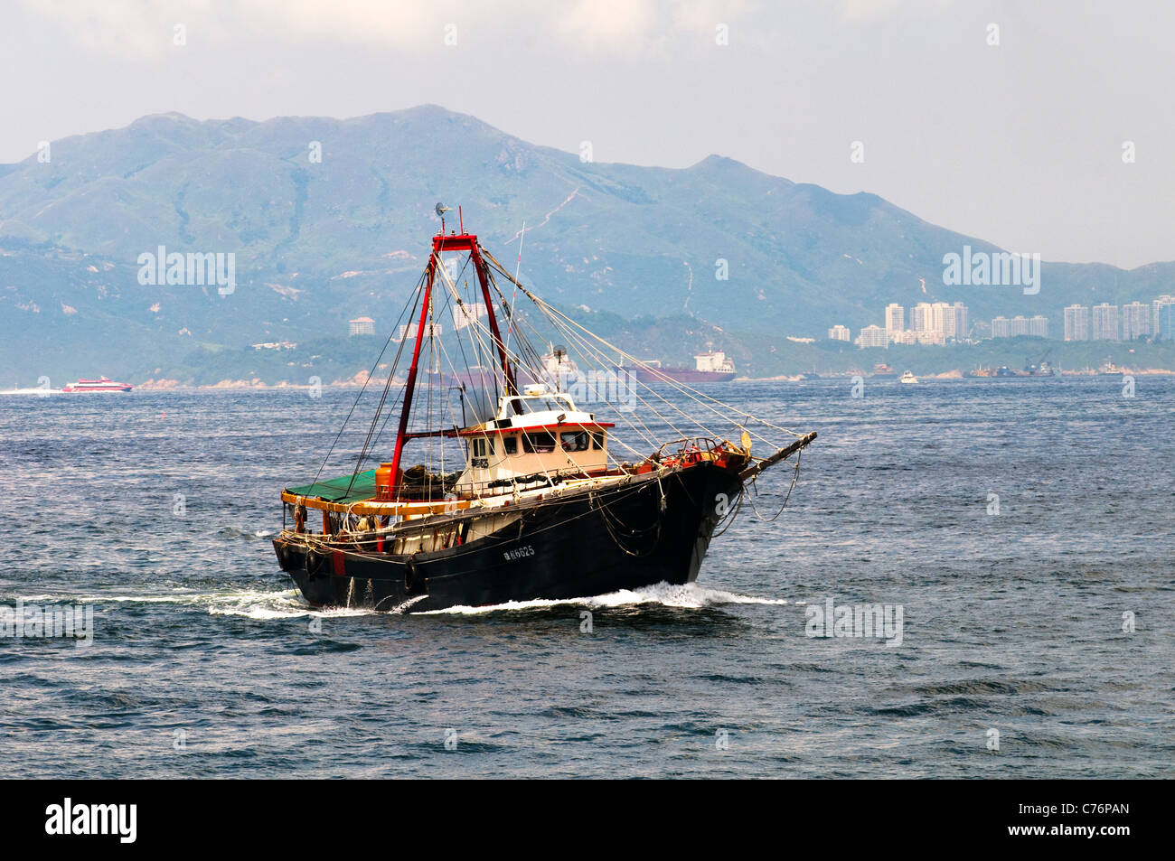 A traditional Chinese style fishing boat in the south China Sea. two big fishing nets are dropped from both sides - Stock Image
