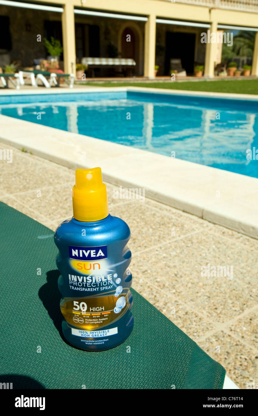 Nivea sun lotion on sun bed, with swimming pool in background. May 2011 - Stock Image