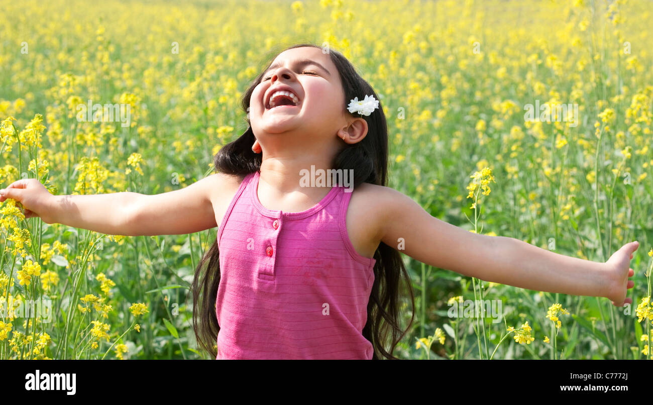 Young girl enjoying herself in a field - Stock Image