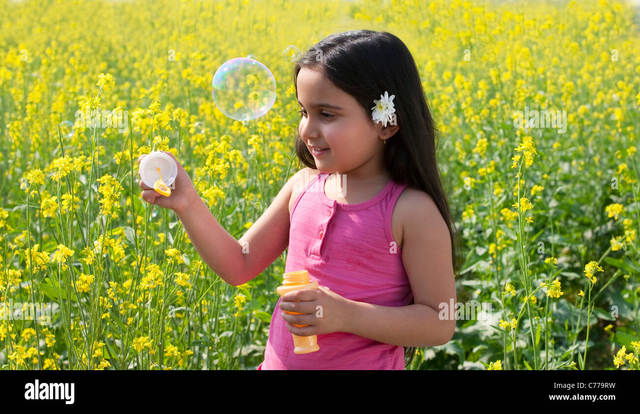 Young girl making bubbles in a field Stock Photo