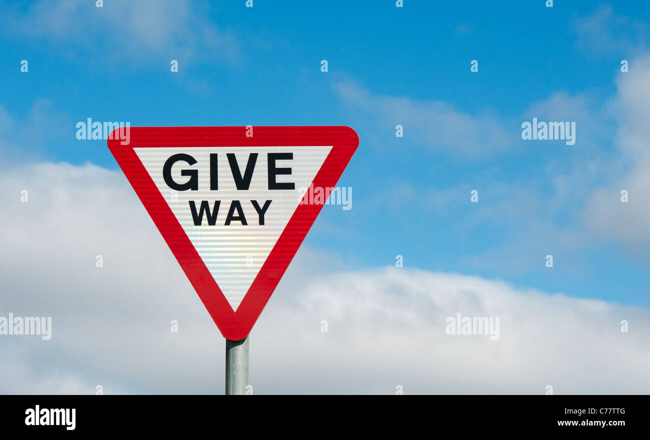 Give way warning road sign against blue cloudy sky. England Stock Photo