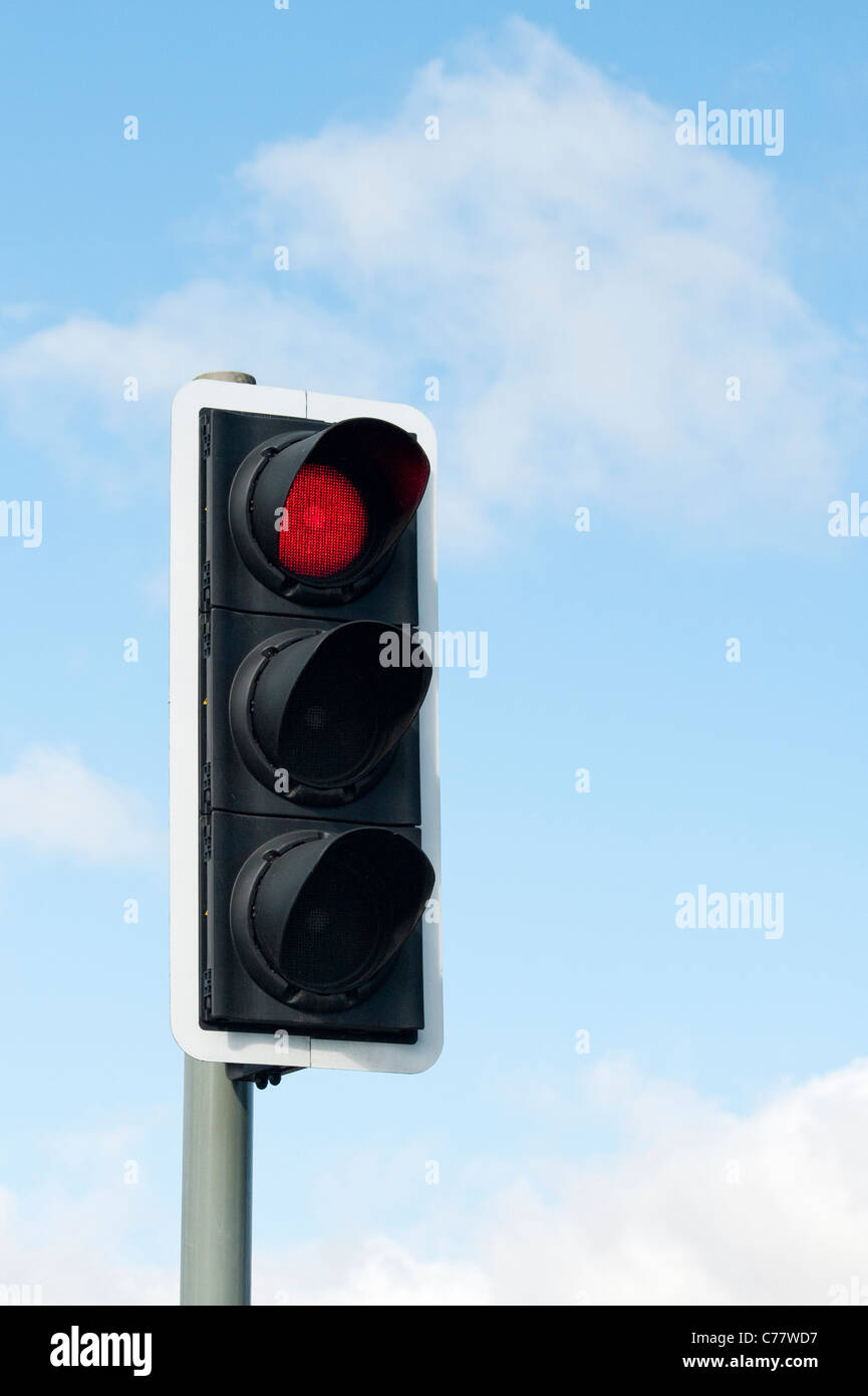 Red Traffic light against blue sky in England Stock Photo