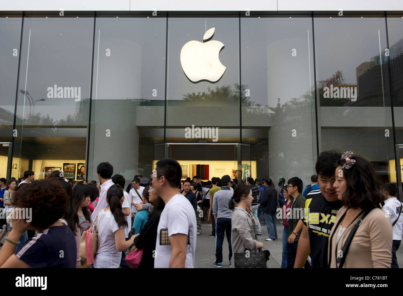 Pedestrians walk past an Apple Inc. store in Beijing, China.11-Sep-2011 - Stock Image