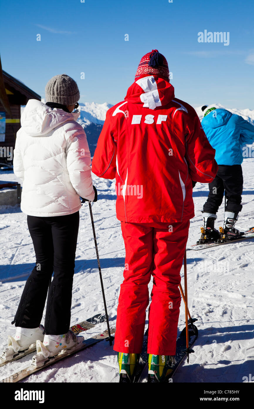 ESF ski instructor with learner, Courchevel 1850, France. - Stock Image