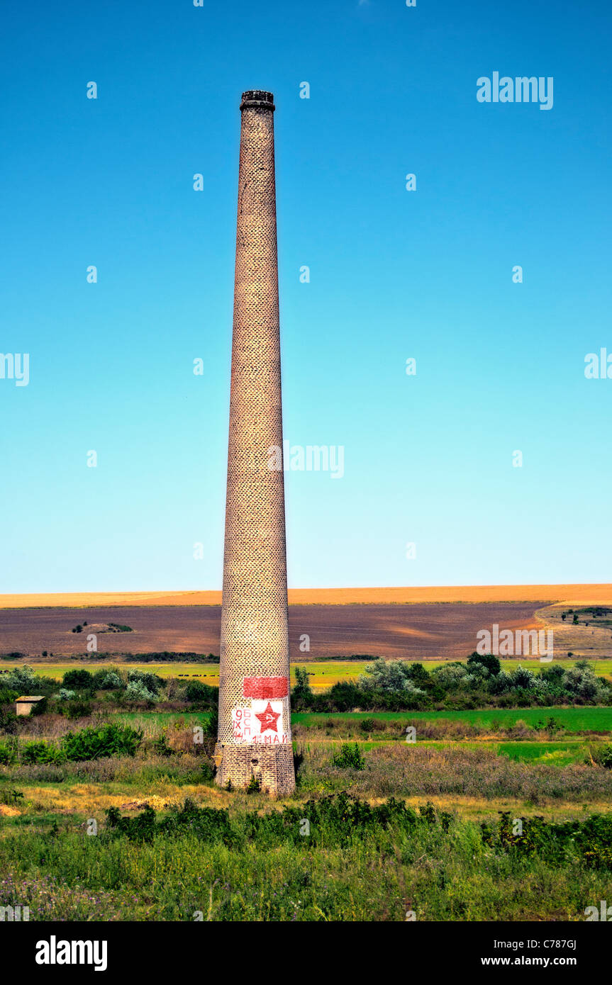 Remains from the communism- chimney with painter red star hammer and sickle - Stock Image