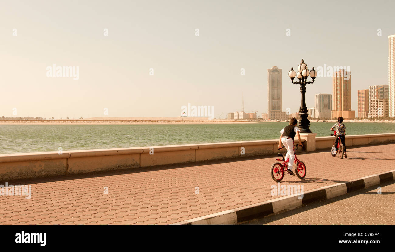 two Arabic kids riding their bikes in Sharjah - Stock Image