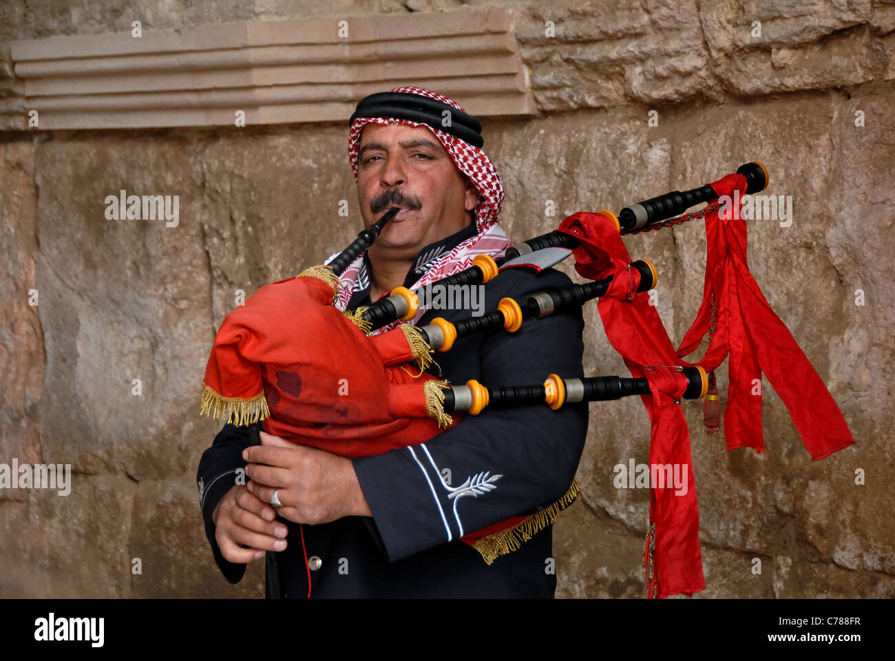 Jordanian bagpiper with a red bagpipe against a wall. Stock Photo