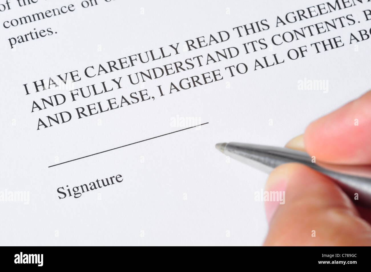 A hand, holding a pen, is ready to sign a document - Stock Image