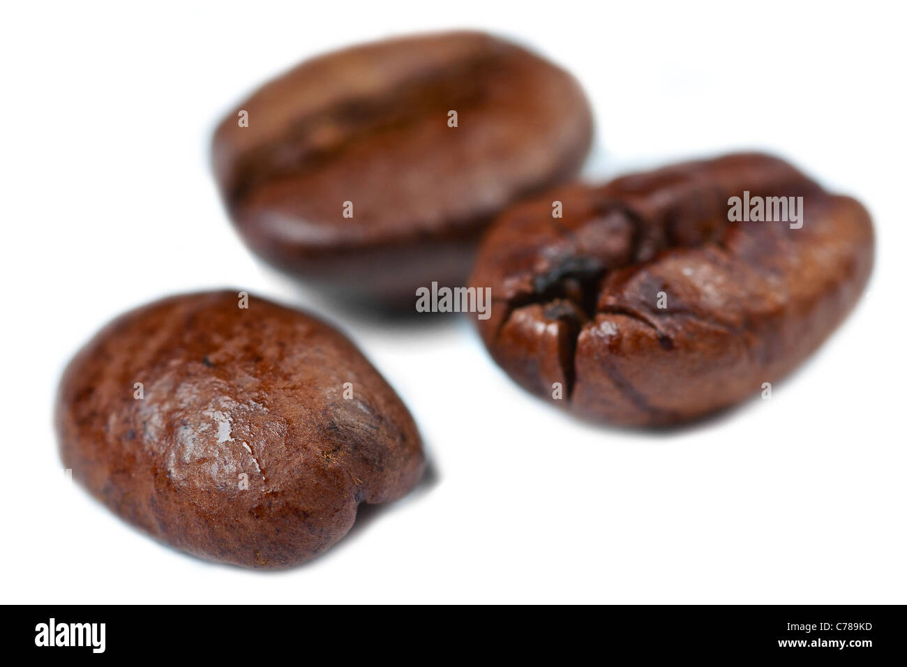 Three coffee beans on a white background with low depth of field. - Stock Image