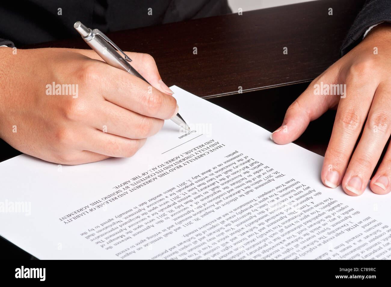 Businesswoman signing a document. - Stock Image