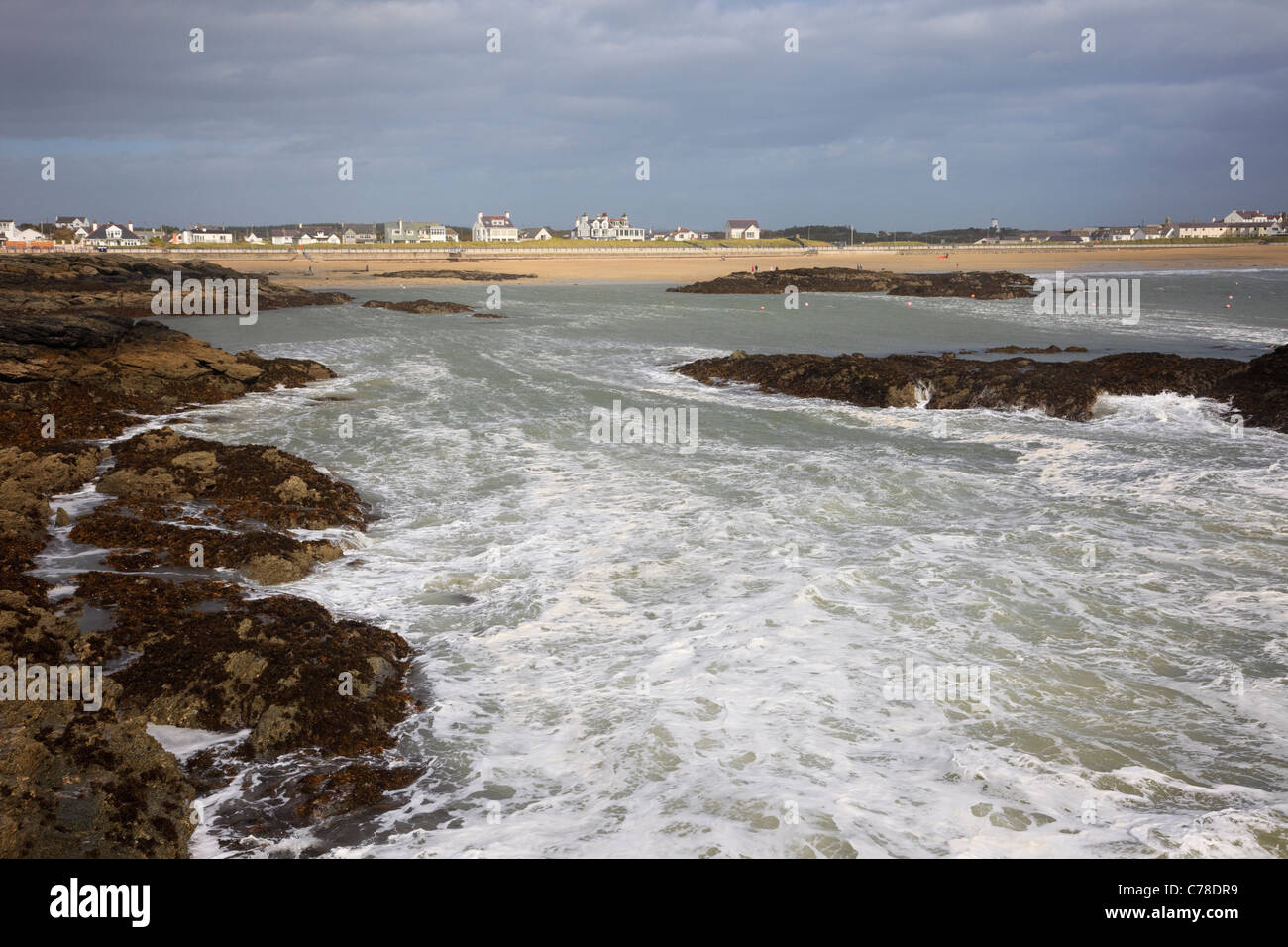 Trearddur Bay, Anglesey, North Wales, UK. View to seafront and beach across the water from rocks - Stock Image