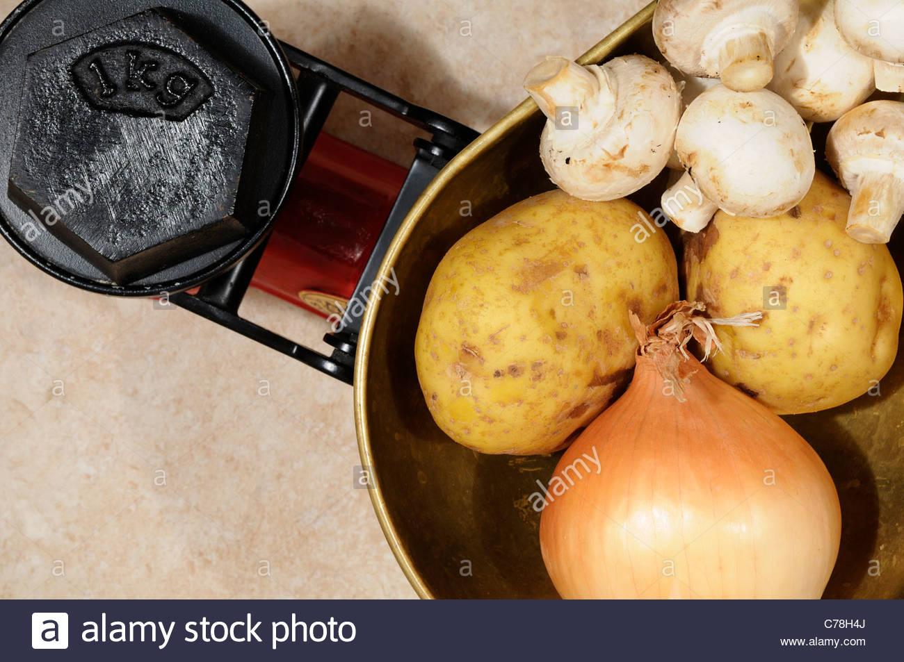Mixed veg on Kitchen scales 1kg, England - Stock Image