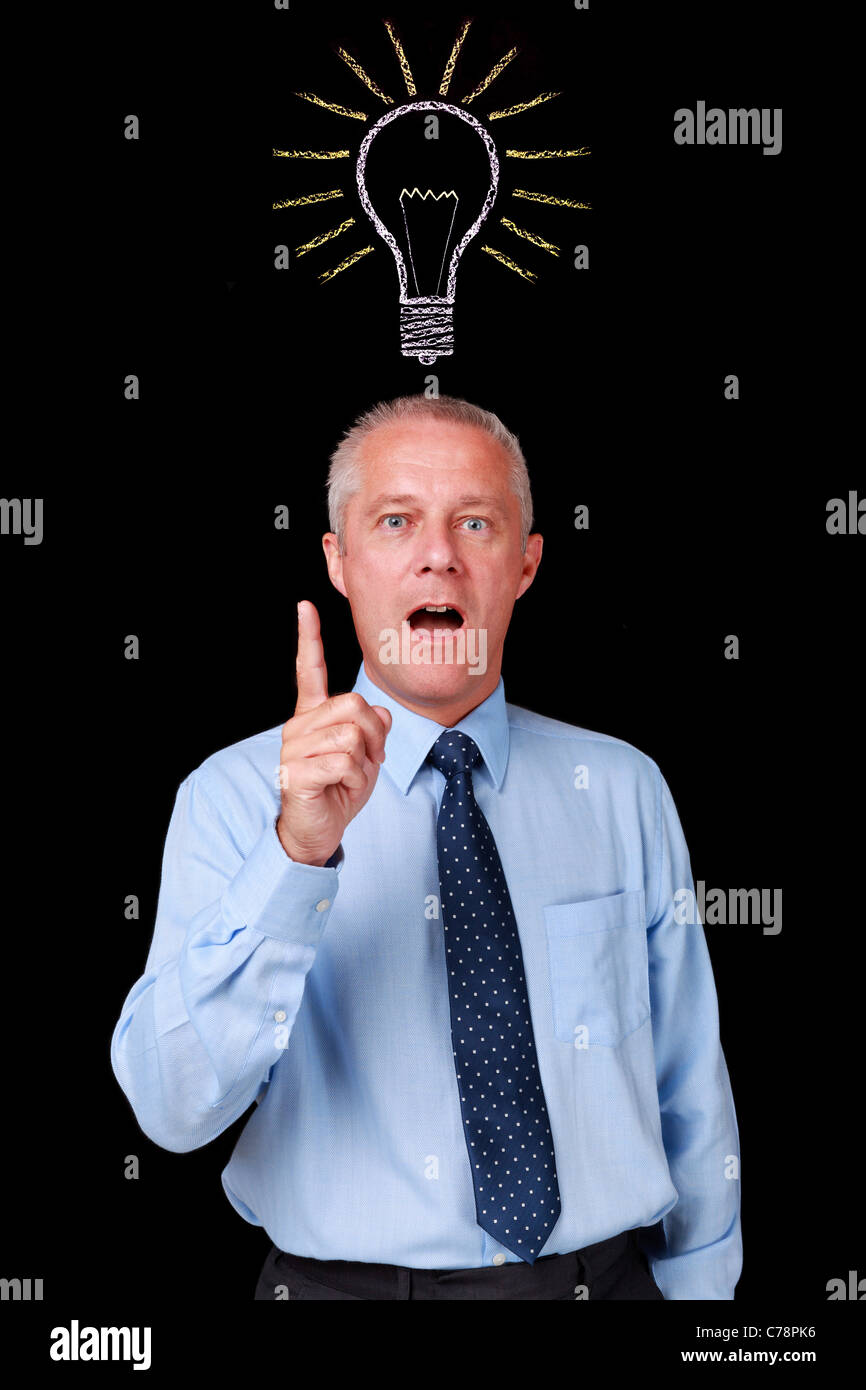 Photo of a mature businessman against a black background with a chalk lightbulb drawn above his head - Stock Image