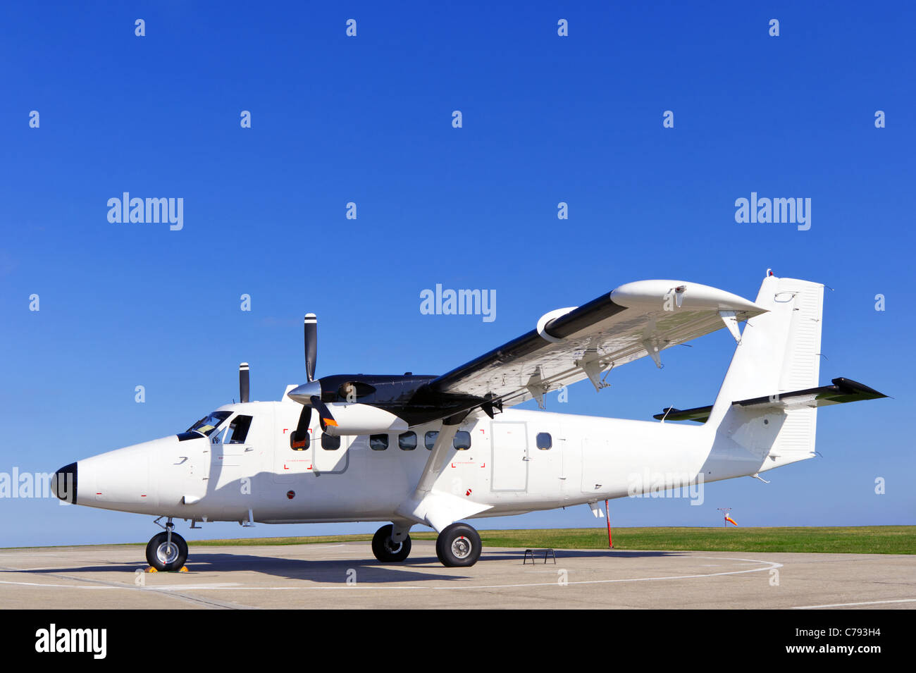 Photo of a twin propeller aircraft stationary on the runway on a bright sunny day with clear blue sky. - Stock Image