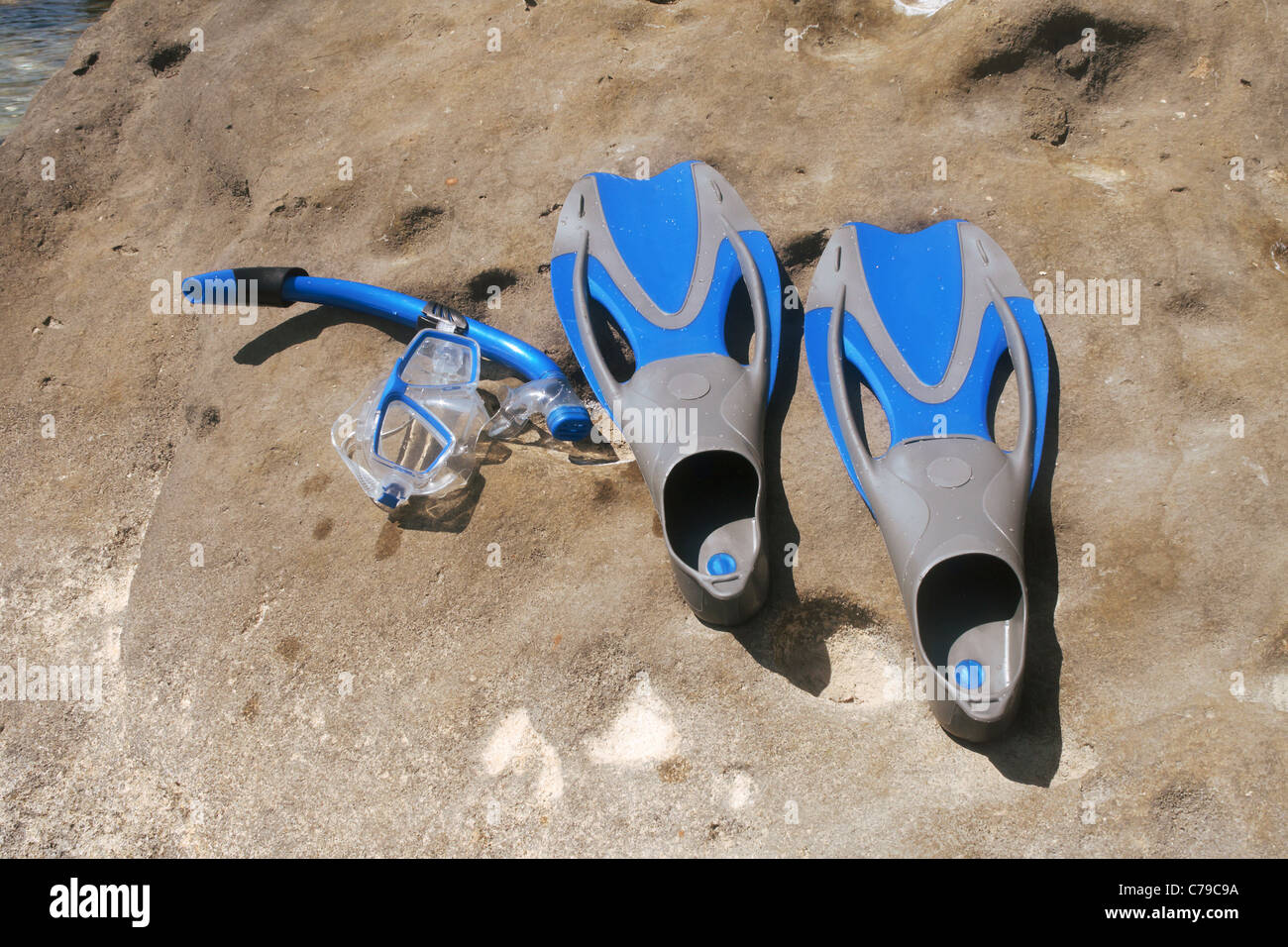 Flippers and snorkel with the mask lying on a rock. - Stock Image