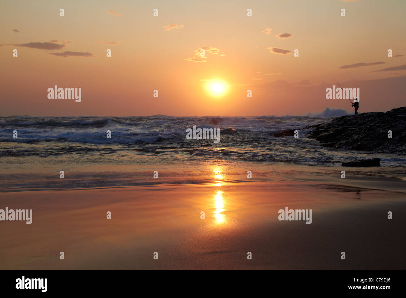 Sunrise over the Indian Ocean with man fishing from the rocks. Amanzimtoti, KwaZulu-Natal, South Africa. - Stock Image