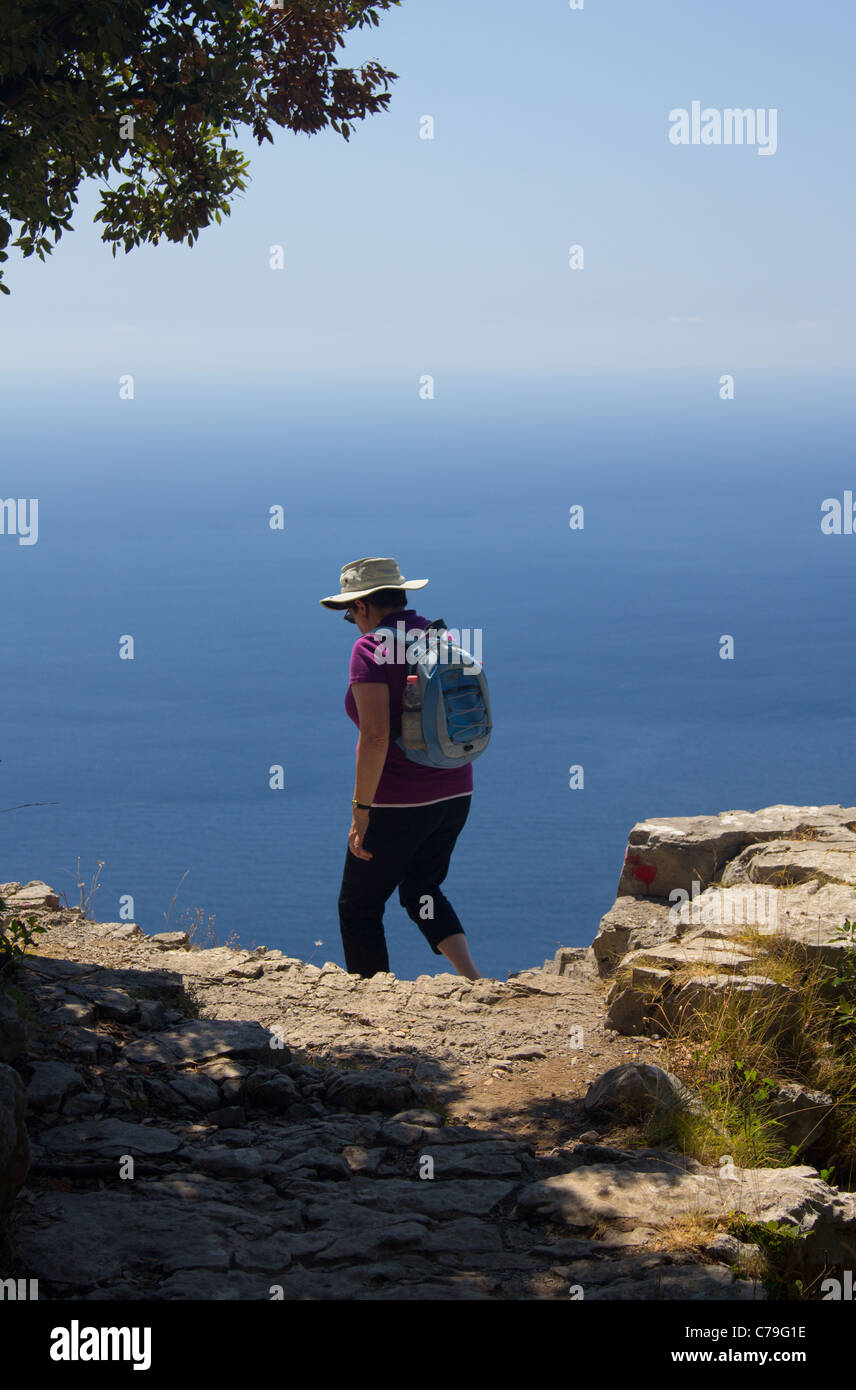 A lady set against the backdrop of a glorious blue sea walking the 'Path of the Gods' above the Amalfi Coastline - Stock Image