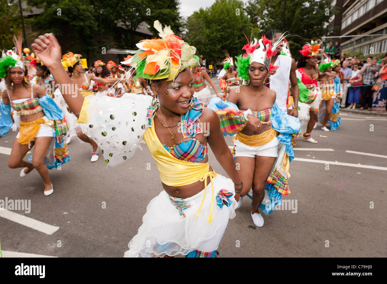 A group of women in colourful costumes dancing in the parade of the Notting Hill Carnival 2011. - Stock Image
