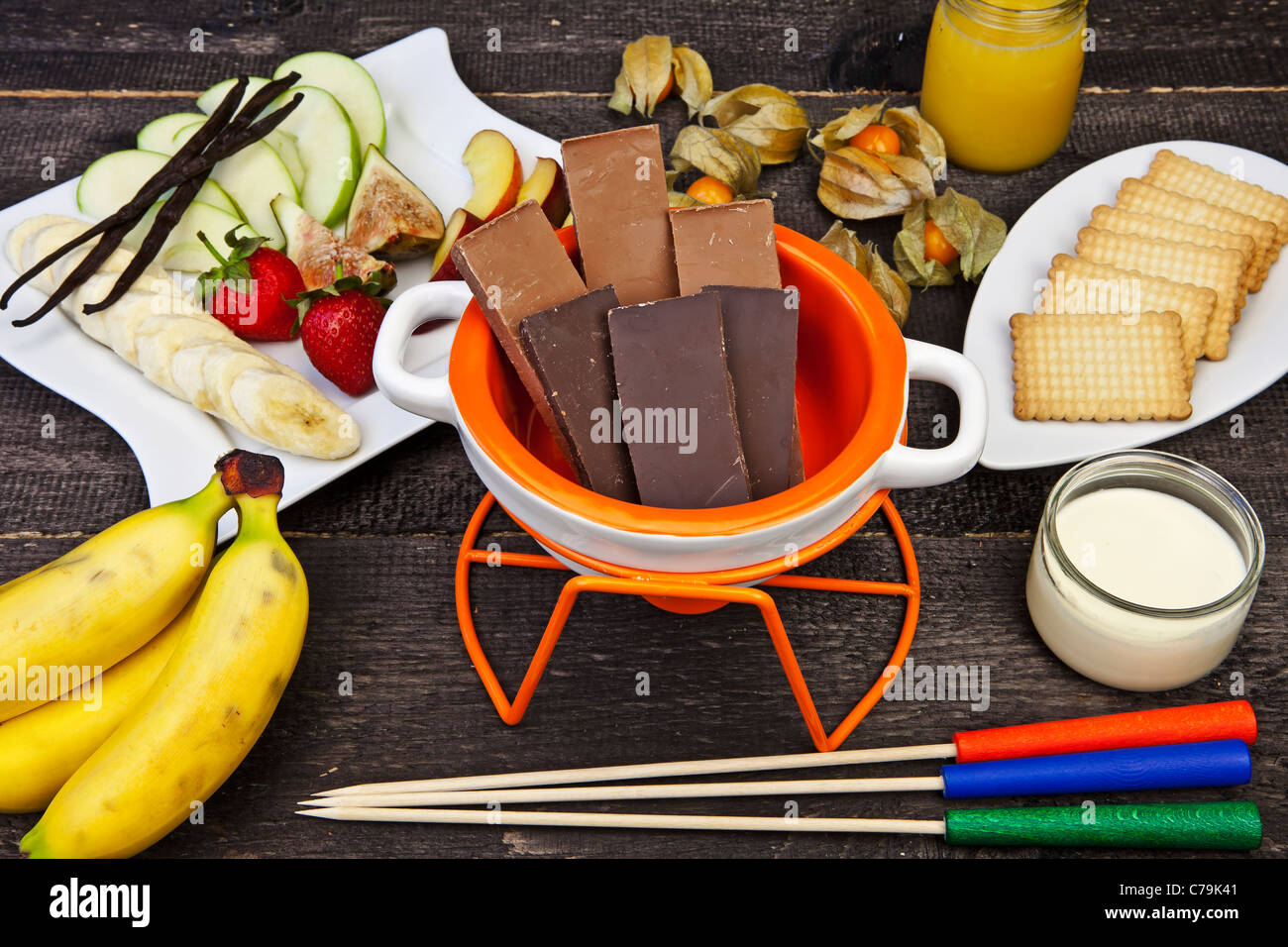 fresh ingredients for a typical Swiss chocolate fondue with fruit and biscuits - Stock Image