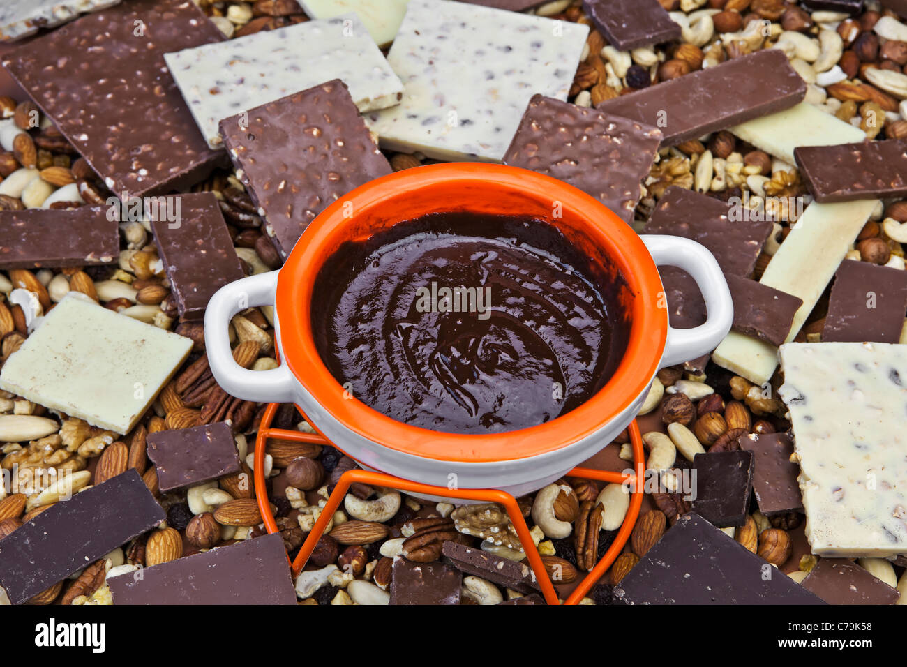 melted chocolate in a fondue pot in the middle of a stack of chocolate pieces - Stock Image