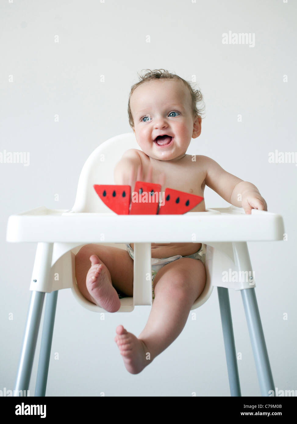 Baby boy (6-11 months) sitting on high chair Stock Photo
