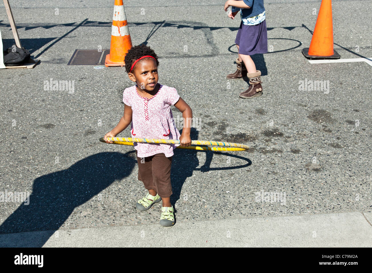 tiny black girl playing with hula hoop in blocked off area of street adjoining market Bellingham Whatcom County Stock Photo