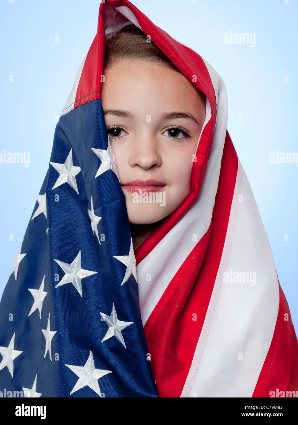 Studio portrait of girl (10-11) wrapped in american flag Stock Photo
