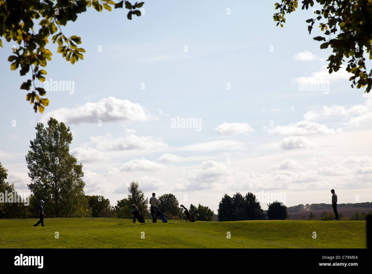 Louth, Lincolnshire, England, three, 3, golfers lining up a shot on crowtree golf course putting green golfing golfers - Stock Image