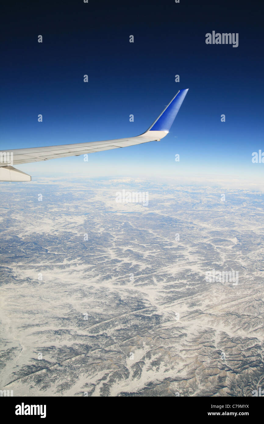 view from an airplane flying over winter mountains with the airline wing visible - Stock Image