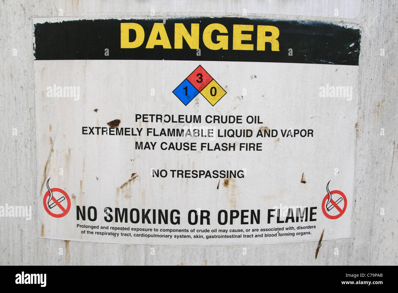 crude oil danger sign on the side of an old crude oil tank - Stock Image