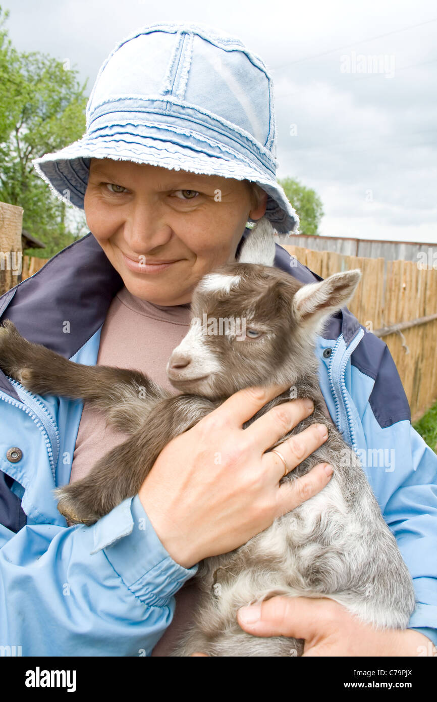 Portrait of the elderly woman holding on hands young goat. - Stock Image