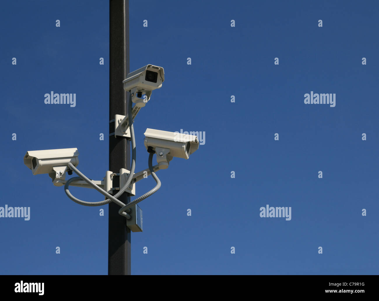 three security video cameras mounted on a pole with a blue sky background and copy space - Stock Image