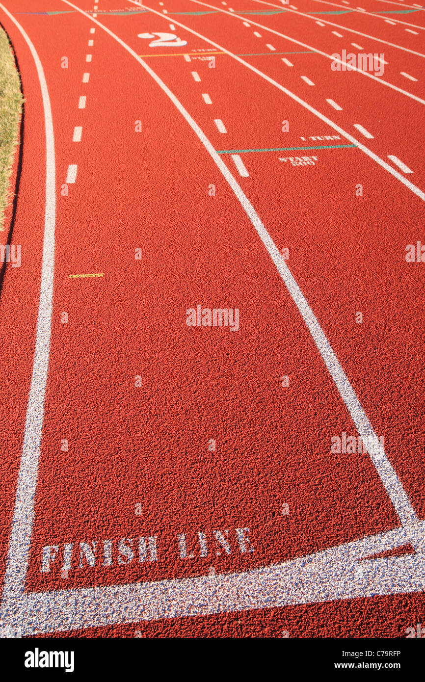 the finish line and start of the turn on a red rubber track - Stock Image