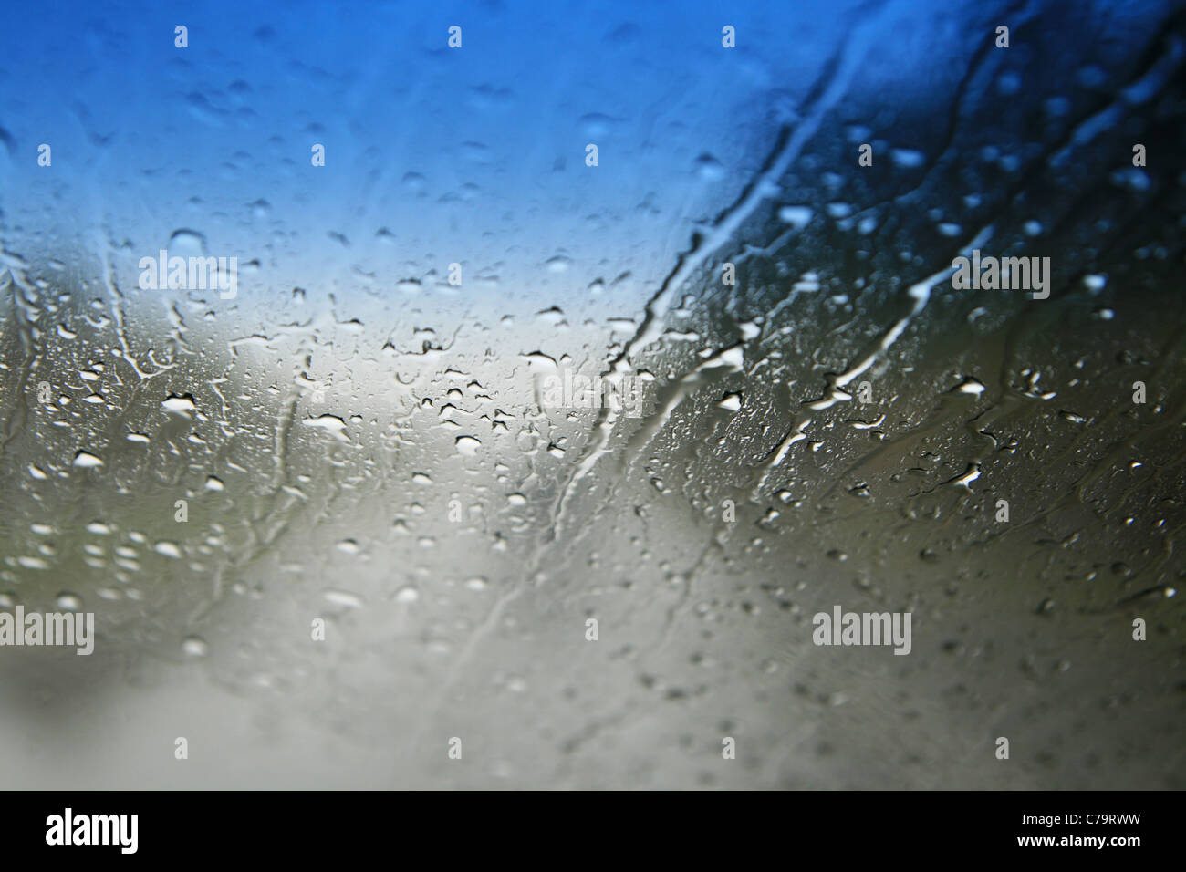 view through a wet car windshield with shallow depth of field and focus on the water drops - Stock Image