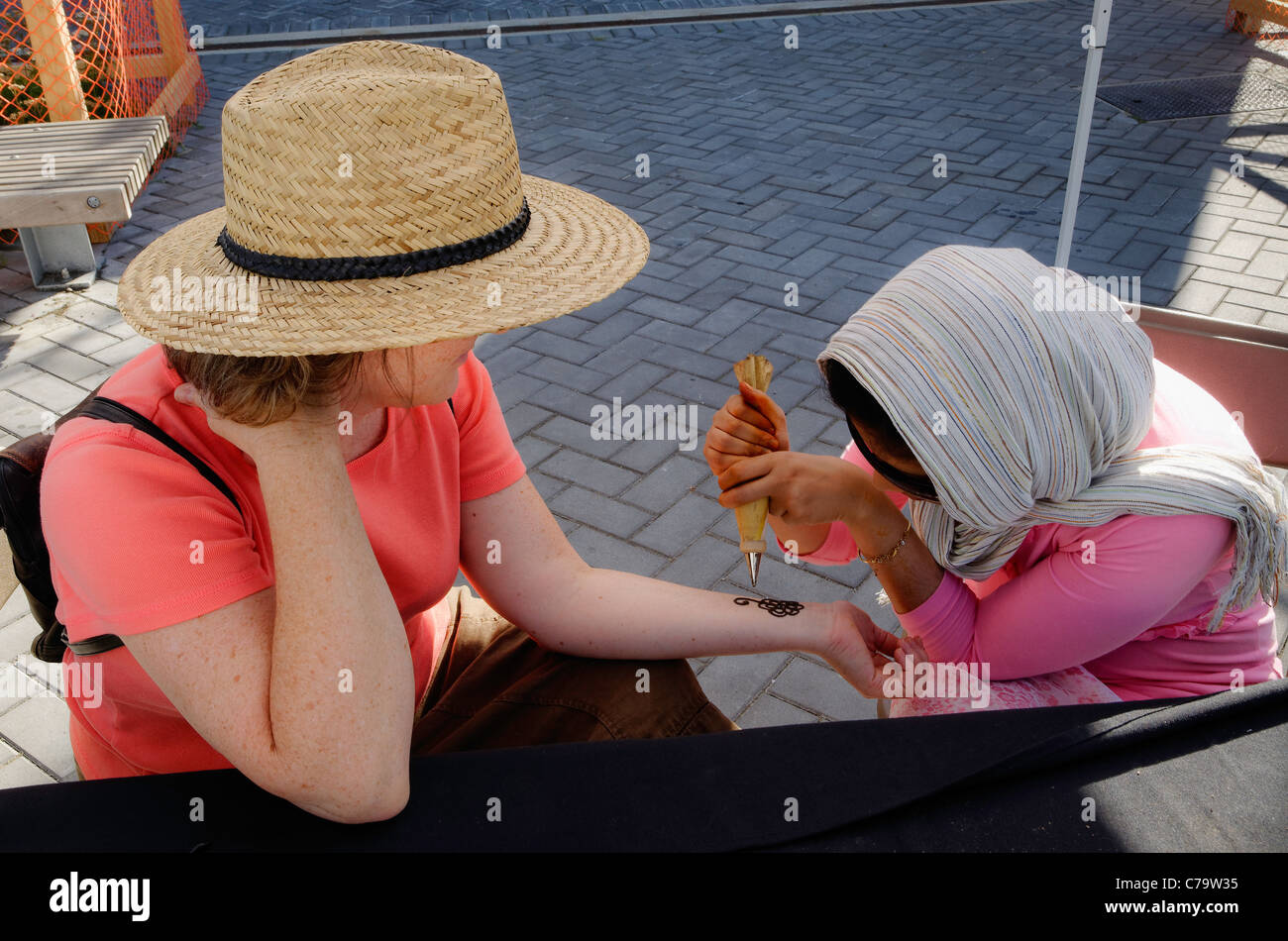 Woman getting mehndi henna on arm, - Stock Image