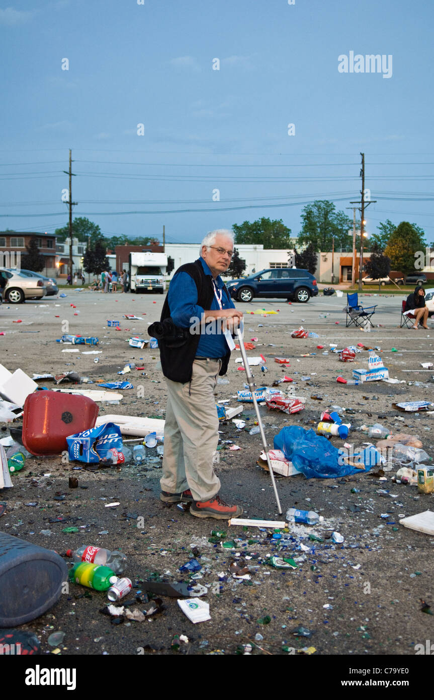 Older Man Standing Amid Trash Left in Parking Lot near Churchill Downs after the 2011 Kentucky Derby in Louisville, - Stock Image